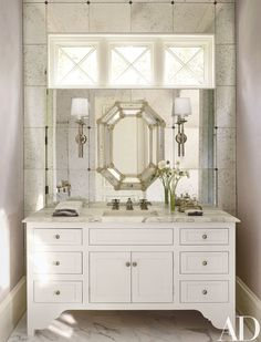 The bath's Palmer Hargrave sconces are mounted on a wall of antiqued mirror; the sink and fittings are by Waterworks.
