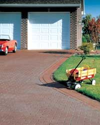 Brick-less driveway. Using templates as large as 6 x 12 feet, an asphalt contractor applied a pattern to warm, newly-laid pavement. The surface was then sprayed with a colored sealer and brushed with a roller that removes excess material from grout lines and creates a skid-resistant texture.