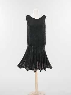 this is a black silk dress from 1926. it has a boyish, boxy shape to it with a raised hemline. The overlapping sequins make for an interesting and unique embellishment. The artist is unknown. Allison Hauke