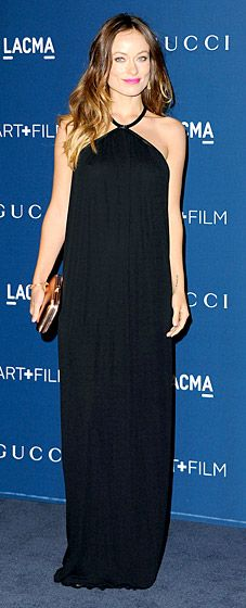 Olivia Wilde disguises her baby bump in a loose, floor-length gown with a halter neck from Gucci.