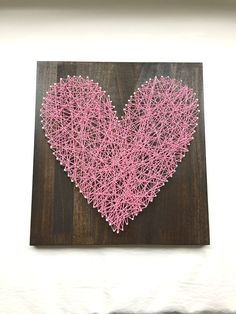 "Light Pink Heart String Art - 12"" x 12"" - Nail and White String Art - Handmade - Ready to Ship - Ready to Hang with Hardware - Home Decor - Wall Art. This beautiful string art is made by me in my home. I start by milling the wood, sanding, then staining the wood. Once dried, I pick a pattern, pound the nails in and tie the string to make this amazing artwork. The popular wood is stained in dark walnut and measures approximately 12"" wide by 12"" tall by 2"" deep. This artwork is made in a…"