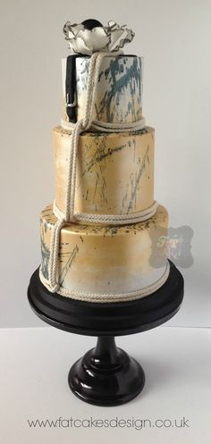 Gold and black wedding cake. With rope , paint splatter and belt. Designed for alternative Brighton wedding fair.