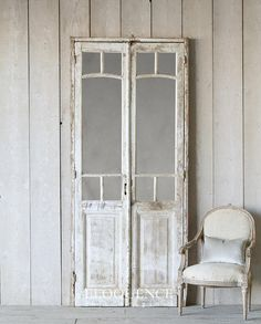 Vintage Mirrored Doors Pretty pair of vintage architectural arched mirrored doors. Old white washed layers of paint with layers of gray and beige underneath. One pair available.