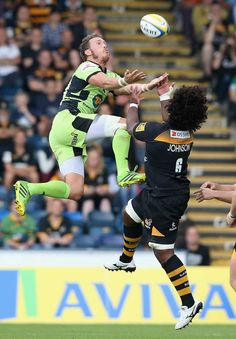 Northampton Saints' James Wilson climbs for the ball alongside Ashley Johnson