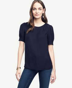 """Tailored to perfection, our softly shirred blouse has sophisticated piping for a feminine finish. Jewel neck. Short sleeves. Shirred sleeve caps. Front and back shirred shoulder yokes. Piped neckline and shoulder yokes. Back keyhole with hook-and-eye closure. Shirttail hem. 26 3/4"""" long."""