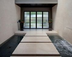 Large steps float above moving water in this inventive courtyard. Frosted-glass doors open from the outside into the water courtyard, and the floating steps lead to the home's front door.