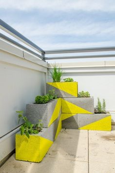 A creative idea for using cinder blocks as a planter wall - enlivened with some bright yellow paint.