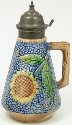 """ESTRUSCAN STYLE MAJOLICA SUNFLOWER SYRUP PITCHER  Etruscan marked Majolica, earthenware syrup pitcher, cobalt, brown, yellow and green slip, with a sunflower motif, and capped with pewter, hinged pour spout. Brown, branch handle and GSH Etruscan Majolica impressed mark on bottom, with """"N"""" impression of decorator"""