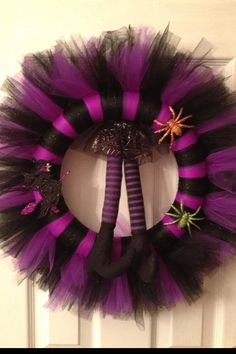 Halloween Witch Tulle wreath. 12 in wreath, black, black glitter and purple tulle. Decorated with coordinating matching glitter spiders, glitter witch and soft witch legs.