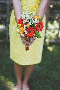 Lemon sherbert colored dress compliments the bright orange bouquet beautifully #orangebouquet