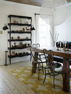 Let's just talk about how much I love this room for a second. I love the chunky table and how it goes with the lighter wood floors. I love the chairs. The rug is cute. And the shelving is absolutely genius. I need to find several identical coffee tables now so I can cut them up and do this.