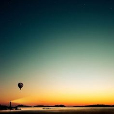 lighthouse. hot air balloon. sunset. ocean.