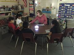A push light on a table with the teacher and a small group of students