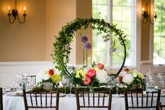 Hoops with cascading greens and clematis, allium, and peonies created dramatic centerpiece for these oval tables.