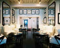 White wingback chairs and black leather stools gathered around circular tables; J.K. Place, Florence