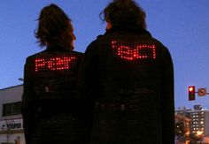 "Jacket Antics - ""two garments that have unique texts and designs scrolling through the LED array on each of the backs. If the wearers hold hands, the LED arrays presents a third, synchronous message that scrolls from one to the other."" By Barbara Layne, Studio subTela, Hexagram Institute"