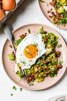 Spicy Pork Brussels Bowls are a delicious low-carb meal, made with shredded brussels sprouts as the base, smoky ground pork, and an egg on top! #brussels #bowls