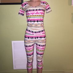 Two Piece Capri Set Pink multicolor cute Aztec print like pattern. The set will fit a medium or large. The set has never been worn, but it lightly worn because it was once in a boutique and was tried on and modeled in a few times. Other than that the condition is very good. The short crop top and Capri leggings are made of 90% polyester and 10% spandex, so the material is very stretchy. Other