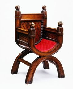Tudor Chestnut Armchair reproduction 1840 by Lewis Nockalls Cottingham. Chairs with legs arranged in an x-shape were used by designers to create Tudor interiors. This chair was based on a medieval chair at York Minster. The Long Gallery at Adare Manor was furnished with medieval-style furnishings, either antique or reproduction, by Lord and Lady Dunraven in 1834. They acquired the 17th-century Flemish carved oak chairs. Victoria and Albert Museum