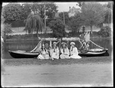 Four unidentified young women, three in sailor type uniforms and one dressed as Britannia, seated in front of a decorated row boat, probably Christchurch district c1910
