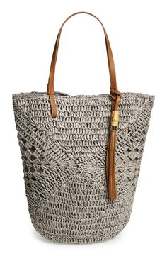 Toting this hand-crocheted bucket bag to the beach! The slouchy silhouette, open geometric patterning, over-the-shoulder handles, and bamboo tassel add so much charm.