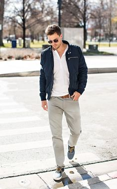 Nail off-duty dressing with this combination of a navy blue bomber jacket and grey jeans. A pair of grey plimsolls will seamlessly integrate within a variety of outfits.   Shop this look on Lookastic: https://lookastic.com/men/looks/bomber-jacket-henley-shirt-jeans-plimsolls-belt-sunglasses/12666   — Dark Brown Sunglasses  — White Henley Shirt  — Navy Bomber Jacket  — Brown Leather Belt  — Grey Jeans  — Grey Plimsolls