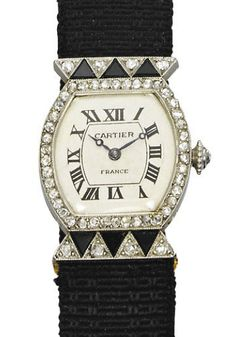 AN ART DECO ONYX AND DIAMOND TORTUE 'DENTS DE LOUP' WRISTWATCH, BY CARTIER.  The oval cream dial with Roman numerals and blued steel hands within a rose-cut diamond crown, to the onyx and diamond triangular-shaped shoulders, on a deployant buckle and black silk strap, mechanical movement, circa 1925, 15.7 cm inner circumference, with French assay marks for gold and platinum  Dial signed Cartier, nos. 3238, 16804 and 8125  Movement numbered 16804  Strap numbered 6318