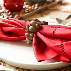 Acorn Place Setting Acorns become table jewelry when they're wired together to make a napkin ring (see directions on the next slide). Bright red napkins stand out against a simple white plate. For a touch of texture to the table, lay down a burlap table runner.