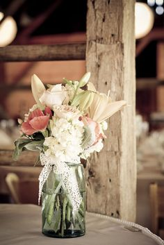 Romantic vintage rustic decor using mason jars, blooms and lace decor. I love this for the tables outside.