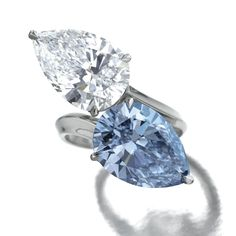 HIGHLY IMPORTANT AND EXCEPTIONALLY RARE DIAMOND RING, ALEXANDRE REZA Of cross over design, set with a fancy vivid blue pear-shaped diamond weighing 5.02 carats and a pear-shaped diamond weighing 5.42 carats, to a platinum mount, size 52, signed A. Reza, French assay and maker's marks.