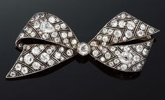 DIAMOND BOW BROOCH, 1920S. Designed as a stylised ribbon bow, the arrow-shaped sections millegrain-set with circular-, single-cut and pear-shaped diamonds.