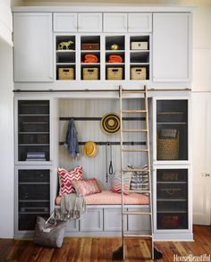 A floor-to-ceiling bank of cabinets by the side door functions as a mudroom, with cubbies for bookbags and soccer balls. The built-in bench cushion is covered in Portico from Thibaut's Portico collection of Sunbrella fabrics. The ladder is by CSH.