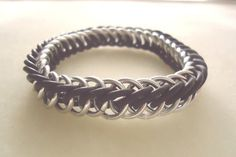 I designed these bracelets as a memorial / show of support for military prisoners of war and those who are missing in action (POW / MIA), and they are made with silver anodized aluminum paired with black rubber connectors (for some stretch), in a simple but versatile half Persian 4-in-1 chainmail weave. As a bonus, I donate 5% of the proceeds from each sale, to the Tragedy Assistance Program for Survivors (TAPS) charity.  Enjoy :)