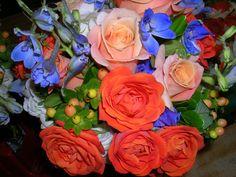 Bright blue delphinium, bright orange roses, peach hypericum berries, peach spray roses