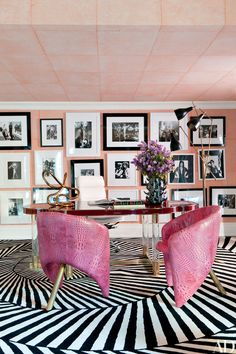 Raspberry leather chairs by designer Kelly Wearstler bring color to the office in a Bel Air, California, home, where a collection of photos is displayed; the tube sculpture on the desk is also by Wearstler, and the carpet was custom made by the Rug Company.