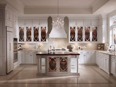 Maple cabinetry in a brilliant Dove White and stunning glass panels gives a contemporary twist on a traditional style in this exquisite transitional kitchen.   Love it!!