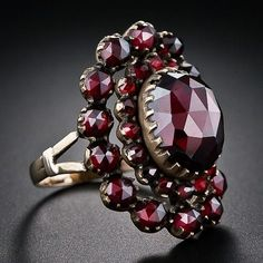 Bohemian Garnet Antique Ring, A sizable high-domed faceted garnet headlines this superb, all original antique Bohemian garnet ring. The center stone is surrounded by a double row of smaller garnets and the ring measures one-inch long Garnet Jewelry, Garnet Rings, Gems Jewelry, Jewelry Box, Jewelery, Fine Jewelry, Antique Rings, Antique Jewelry, Vintage Jewelry
