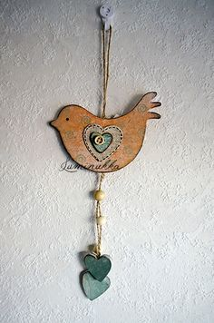 Puinen, rustiikkisen persikansävyinen linturiipus spiraalikoristein ja kaiken kruunaavalla nappisydämellä. Kokonaispituus 30 cm // Wooden, shabby chic-styled peachy pink bird with spiral decorations and a cute button heart. Total length 30 cm.
