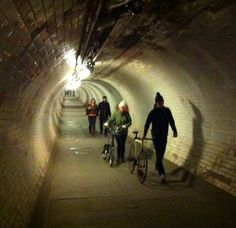 Greenwich Foot Tunnel. Pedestrian tunnel under the Thames designed by Sir Alexander Binnie, linking Greenwich town centre in the south with Island Gardens Park in the north. It is 1,215 feet (370.2 m) long and 50 feet (15.2 m) deep. The tunnel is classed as a public highway and by law is kept open 24 hours a day. It is accessible by spiral staircases and large lifts.