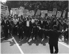 March on Washington for Jobs & Freedom taking place on Constitution Ave. as march organizers link arms in front: Martin Luther King, Jr. Rabbi Joachim Prinz A. Philip Randolph Roy Wilkins & Whitney Young et al.
