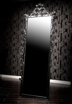 Baroque Mirror - This extremely tall mirror emulates rock-star style and glamor. Featuring an ornately carved Baroque frame painted in a shiny black finish, it mixes elegance with edginess, accumulating in a fabulously unique mirror. Its sheer height means that it brings a certain drama and presence to your house that not many mirrors can match. BLACK  32 IN W 3 IN D 89 IN H 63 LBS