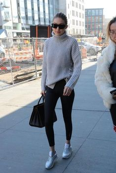 Gigi Hadid wearing Reebok x Face Stockholm Classic Leather Spirit Sneakers in Silver Presence, Saint Laurent Classic Sac De Jour Leather Tote, Missguided Grey Chunky Lace Up Side Turtleneck Sweater, Reebok Studio High Shine Tights and Alain Mikli A05029 Sunglasses