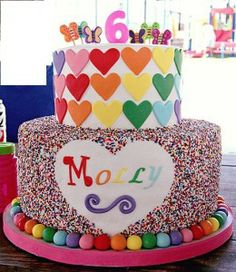 Love this- think we should do the bottom layer white ganache round cake with rainbow hearts, then the top layer a heart shaped cake covered in hundreds and thousands and trimmed with rainbow colour rounds sweets like this!!