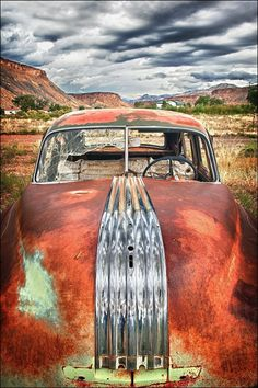 Photograph of an old rusty red and chrome colored abandoned Pontiac car in a field at a small ghost town in Utah. 11x14 16x20 16x24 20x30 24x36 32x48 large gallery wrapped canvas or print sizes. Image title: Reflecting the Approaching Storm This image is from my photography series of objects from the past. Many of my images in this series include old cars or rusty trucks. All photographs are original and photographed by artist Bob Estrin. Photographs are available in a variety of sizes as…