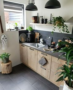 The kitchen of today - graphite coloured walls and workspace, offset by stark white, gleaming copper and lush green accents