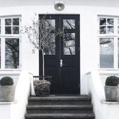 Weißes Haus mit dunkler Holztür