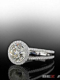 Bez Ambar Round brilliant center diamond with knife edge split shank pave mounting.