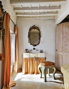The mirror that surmounts the sink in a Roman home designed by Axel Vervoordt is 18th-century Italian, as is the polychrome stool.