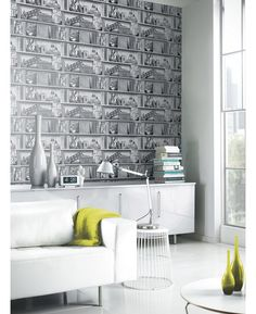 This quirky Upcycle Wallpaper will add a fun and contemporary feel to your home. The design features a bookshelf theme with artefacts including books, reclaimed signs and vintage suitcases in tones of silver, black and grey with a metallic sheen.