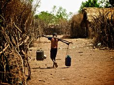 Child carrying water in refugee camp.